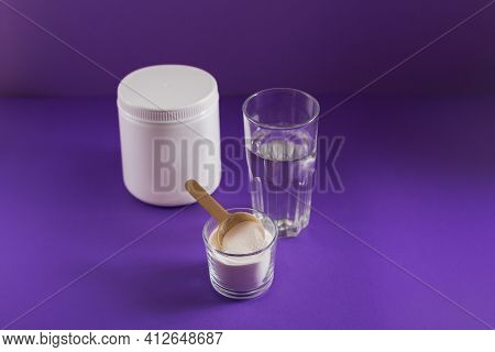 Glass With Collagen Dissolved In Water And Collagen Protein Powder On Purple Table. Healthy Lifestyl