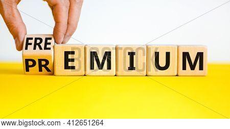 Premium Or Freemium Symbol. Businessman Turns The Wooden Cube, Changes The Word 'premium' To 'freemi