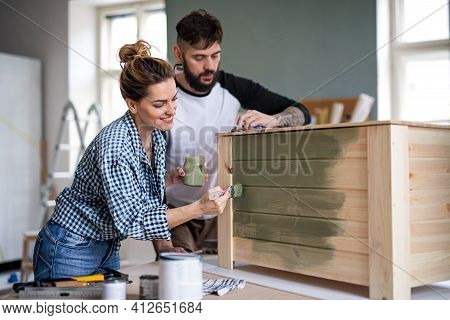 Mid Adults Couple Painting Furniture Indoors At Home, Relocation And Diy Concept.