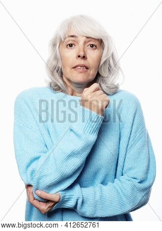 Healthcare and medicine concept: Elderly woman in a blue sweater pain in the elbow health problems over white background