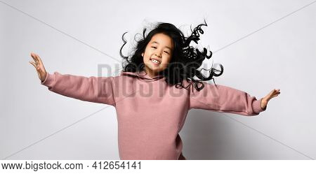 Cheerful Korean Girl In A Warm Dusty Pink Jumpsuit And Sneakers Is Dancing, Smiling Cheerfully On A