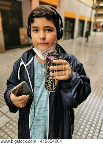 Málaga, Spain - February 22, 2021: View Of Boy Drinking Rockstar And Using Cell Phone With Mask Lowe