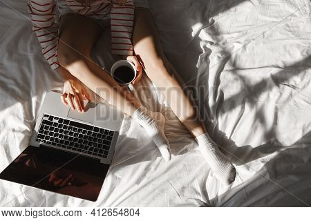 Top View Of Young Woman Using Laptop In Bed, Drinking Coffee And Resting At Home. Cropped Shot Of Fe