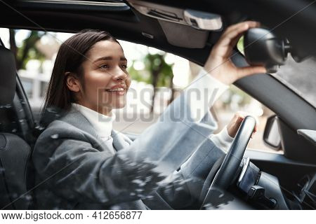 Elegant Businesswoman Looking At Rear Mirror, Adjusting It For Driving. Female Executive Drive Her C