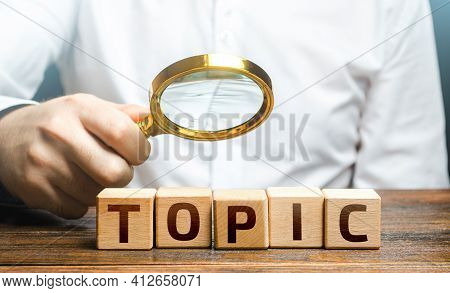 Man Examines Blocks With Topic With A Magnifying Glass. Conduct Research, Get An Topic Explanation.