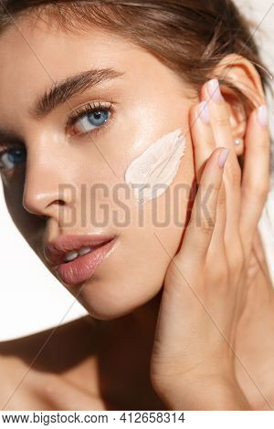 Face Skin Care. Woman Applying Cosmetic Cream On Clean Hydrated Skin Portrait. Beautiful Happy Smili
