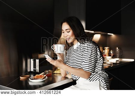 Enjoying Time At Home. Beautiful Young Asian Woman Drinking Coffee While Sitting In The Kitchen And