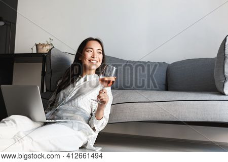 Beautiful Asian Woman Drinking Wine And Using Laptop, Sitting On Floor And Resting At Home