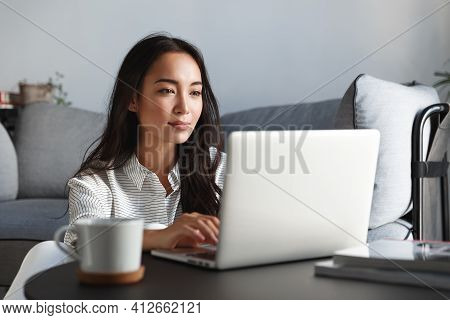 Young Ambitious Asian Girl Working Remote From Home, Looking At Laptop Screen And Smiling. Woman Che
