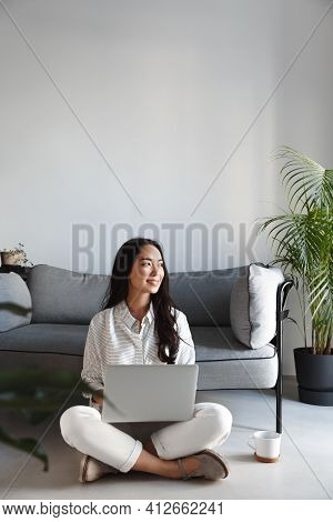 Vertical Shot Of Creative Young Asian Woman Freelancer, Working With Laptop And Looking Outside Wind