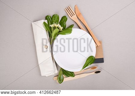 Paper Plate, Wooden Toothbrushes, Cotton Bag, Fresh Green Leaves On A Gray Background.eco-friendly F