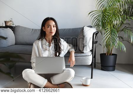 Portrait Of Ambitious Beautiful Asian Woman Working From Home, Sitting Comfortable On Floor With Cup
