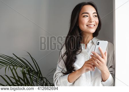Portrait Of Attractive Modern Asian Woman Looking Outside Window And Smiling Dreamy, Holding Smartph