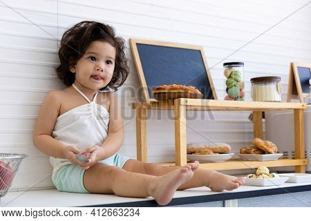 Child Girl Eating Ketchup With Food And Sweets In The Kitchen At Home.
