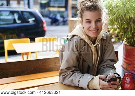 Beautiful Smiling Girl Sitting In Cafe Outdoor Table. Woman Using Mobile Phone While Waiting For Fri