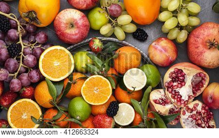 Assorted Fruits. Different Fruits On A Gray Background, The Whole Surface Is Covered With Citrus Fru