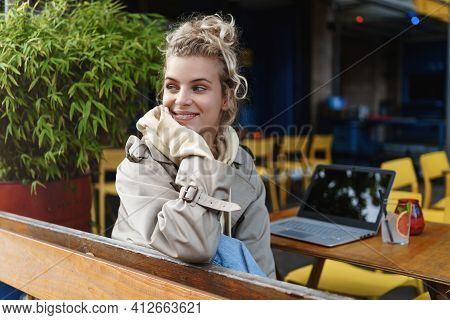 Rear View Pretty Smiling Girl Sitting Outdoor Cafe And Watching Passersby, Looking At Street, Having