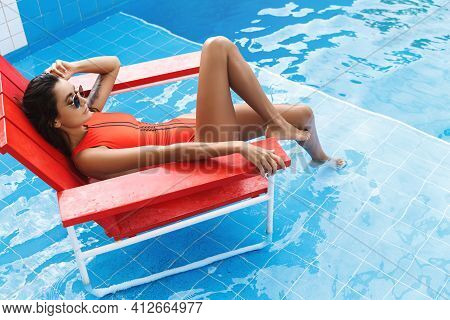 Sexy Woman In Sunglasses And Red Baywatch Swimming Suit, Relaxing In Lifeguard Chair Near Hotel Pool