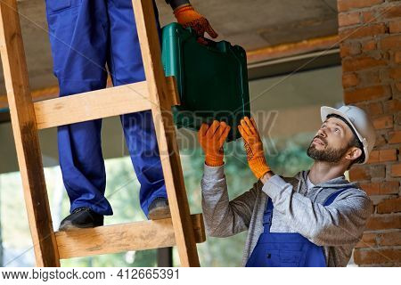 Close Up Of Young Workman In Overalls And Hard Hat Giving Toolbox To His Colleague On Ladder While W