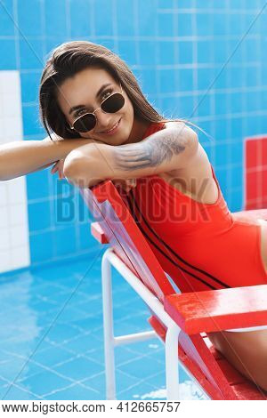 Vertical Close-up Of Sexy Woman In Red Swimsuit, Lean On Lifeguard Chair And Smiling Camera. Attract