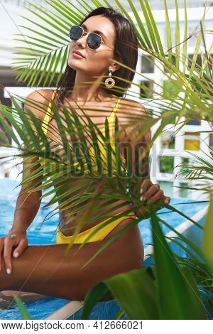 Vertical Shot Of Sensual Woman In Bikini, Posing With Palm Tree Leaves Near Poolside. Young Sexy Tan