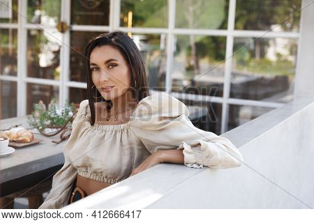Attractive Stylish Woman Sit Outdoor Cafe Table, Eating Croissant And Drinking Coffee. Sexy Female M