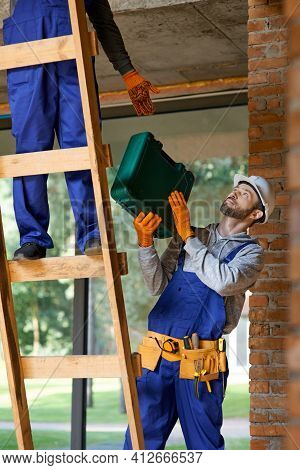 Young Workman In Overalls And Hard Hat Giving Toolbox To His Colleague On Ladder While Working At Co