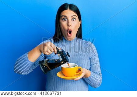 Beautiful brunette woman holding french coffee maker pouring coffee on cup afraid and shocked with surprise and amazed expression, fear and excited face.