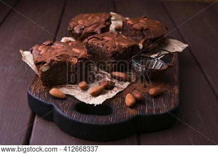 Brownie, Chocolate Cakes With Almonds On A Wooden Board, Sprinkled With Cocoa. Served Homemade Cakes