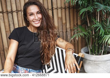 Smiling Woman Sitting On Veranda And Looking Happy. Girl With Golden Tan Enjoying Tropical Sun And S