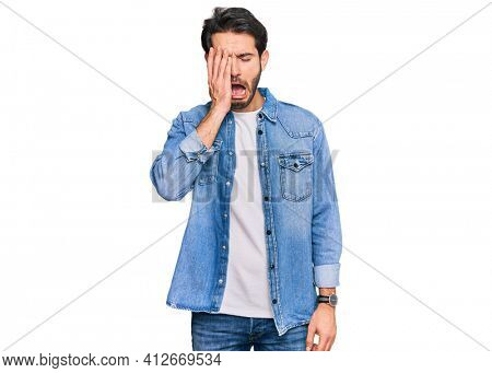 Young hispanic man wearing casual clothes yawning tired covering half face, eye and mouth with hand. face hurts in pain.