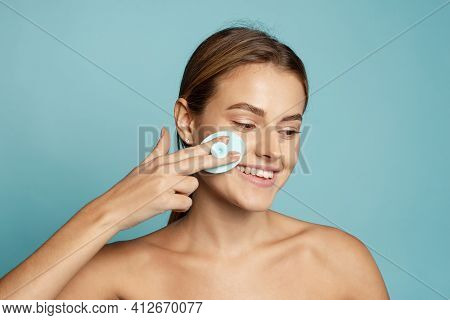 Young Woman Using Using Silicone Facial Cleansing Brush On Blue Background. Skin Care Concept. Beaut