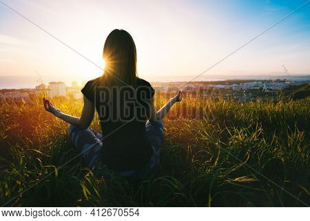 Woman Doing Yoga And Meditates On The Grass On The Top Of The Mountain With Beautiful View At Sunset