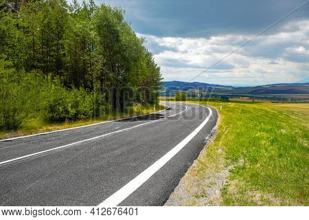 Asphalt road through green hills and clouds in the blue sky