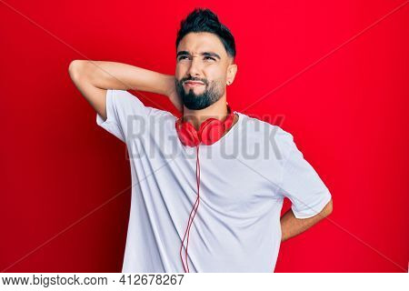 Young man with beard listening to music using headphones suffering of neck ache injury, touching neck with hand, muscular pain