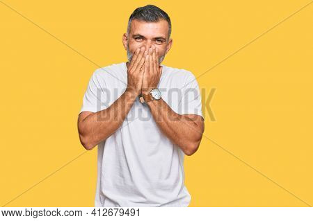 Middle age handsome man wearing casual white tshirt laughing and embarrassed giggle covering mouth with hands, gossip and scandal concept