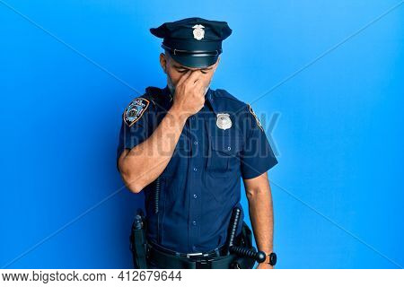 Middle age handsome man wearing police uniform tired rubbing nose and eyes feeling fatigue and headache. stress and frustration concept.
