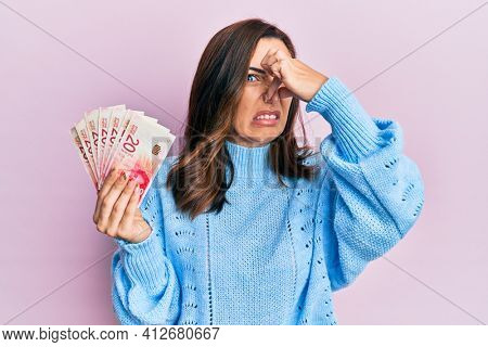 Young brunette woman holding 20 israel shekels banknotes smelling something stinky and disgusting, intolerable smell, holding breath with fingers on nose. bad smell