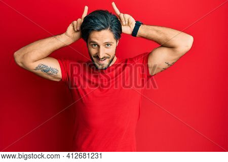 Young hispanic man wearing casual red t shirt posing funny and crazy with fingers on head as bunny ears, smiling cheerful