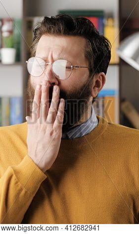 Man Yawns. Tired Sad Bearded Man In Glasses In Office Or Apartment Room Yawns, He Covers His Mouth W