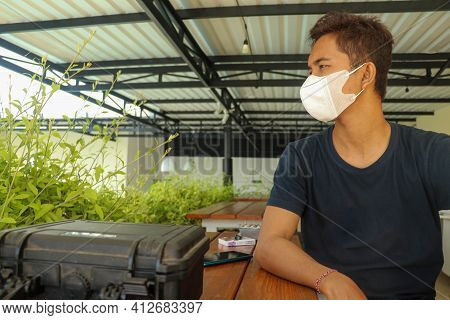 View From Side. Closeup Shot Of An Indonesian Young Man Using A Medical Mask During The Covid-19 Pan