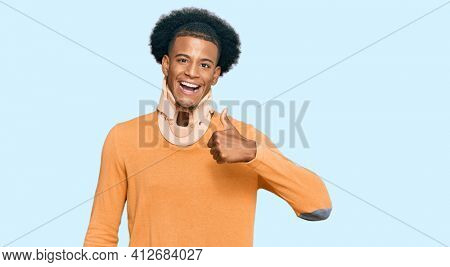 African american man with afro hair wearing cervical neck collar doing happy thumbs up gesture with hand. approving expression looking at the camera showing success.