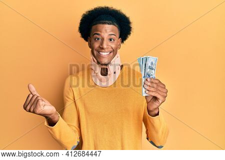 African american man with afro hair wearing cervical neck collar and holding money from insurance screaming proud, celebrating victory and success very excited with raised arm