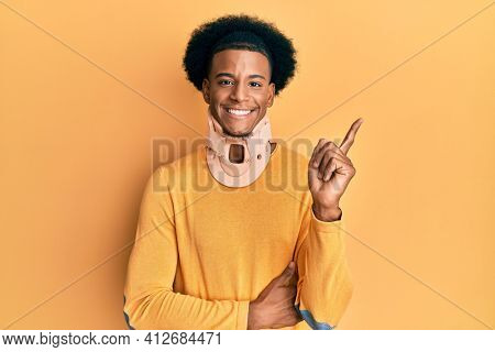 African american man with afro hair wearing cervical neck collar smiling happy pointing with hand and finger to the side