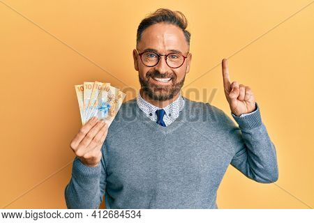 Handsome middle age man holding swiss franc banknotes smiling with an idea or question pointing finger with happy face, number one