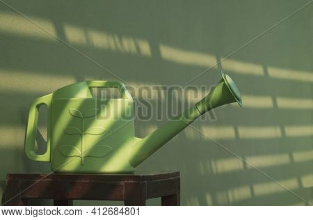 Perspective Side View Of Plastic Watering Can On Wooden Chair With Sunlight And Shadow Of Sunshade B
