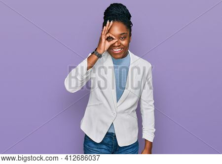 Young african american woman wearing business clothes doing ok gesture with hand smiling, eye looking through fingers with happy face.