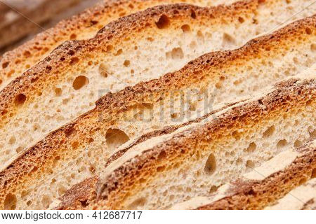 Slices Of Fresh Baked Crusty Traditional Loaf Of Rye Or Wheat Bread