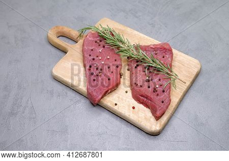 Raw Beef Steak With And Rosemary On Gray Background. Fresh Meat Rib Eye Steak. Cooking Beef Steak Fi