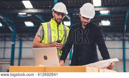 Two Factory Workers Working And Discussing Manufacturing Plan In The Factory . Industry And Engineer